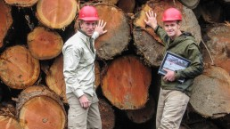 IWC People, Two IWC employees standing in front of logs